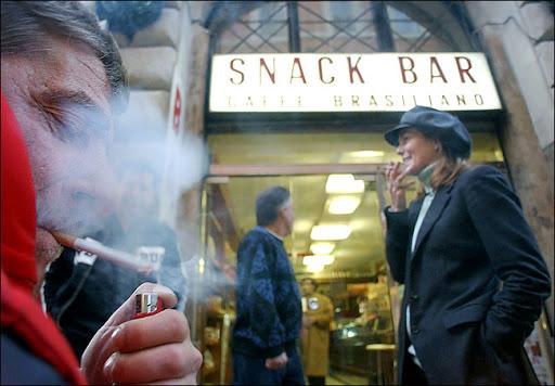 people smoking outside an italian bar